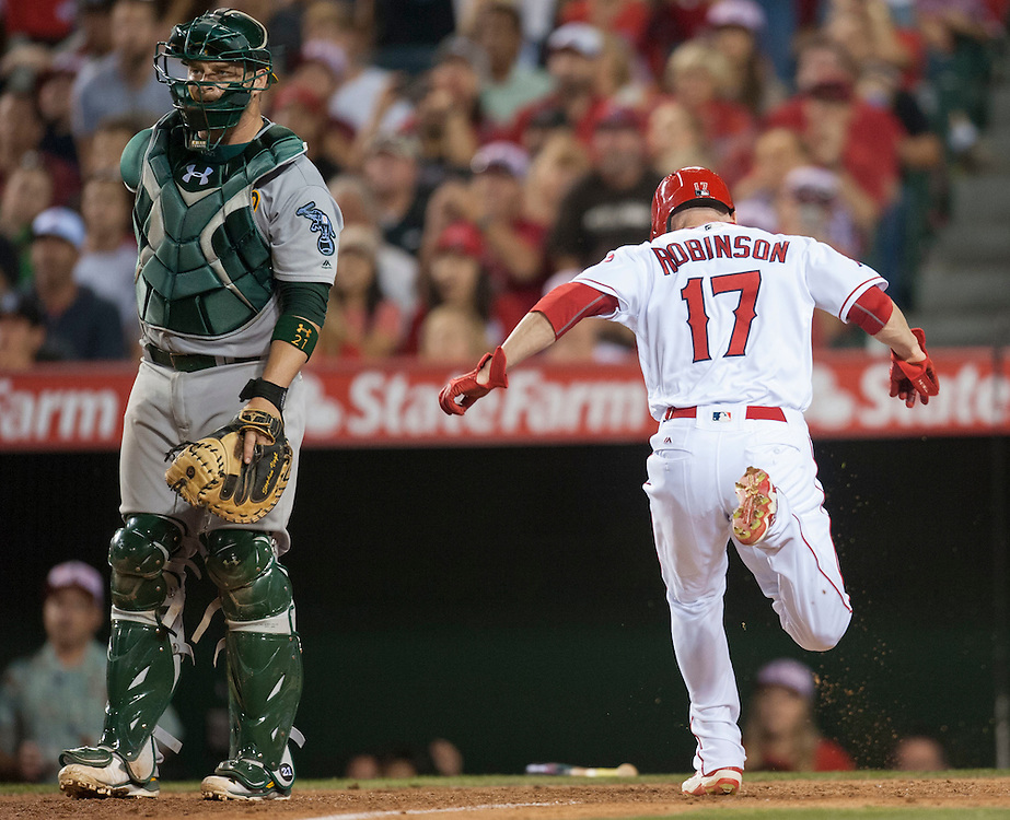 The Angels' Shane Robinson scores past Oakland catcher Stephen Vogt in the fourth inning at Angel Stadium on Friday.<br /> <br /> ///ADDITIONAL INFO:   <br /> <br /> angels.0625.kjs  ---  Photo by KEVIN SULLIVAN / Orange County Register  --  6/24/16<br /> <br /> The Los Angeles Angels take on the Oakland Athletics Friday at Angel Stadium.<br /> <br /> <br />  6/24/16