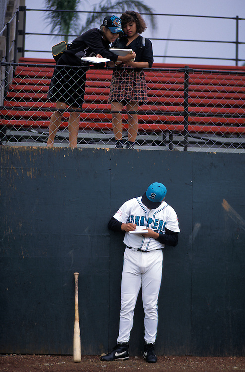 OAXACA, MEXICO: A player for the Saltillo Saraperos signs autographs for a couple of young fans before a game in Oaxaca.