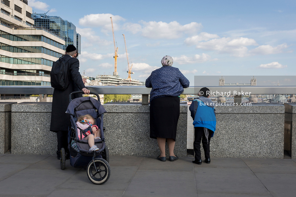 A Jewish family look at the view of the River Thames and in the distance, Tower Bridge, from London Bridge, on 19th April, in the City of London, England.