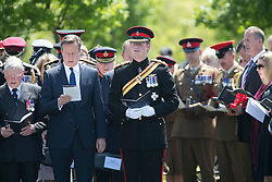 © Licensed to London News Pictures. 11/06/2015. National Memorial Arboretum, Alrewas, Staffordshire, UK. The service to mark the Rededication of the Bastion Memorial. The memorial was begun in Helmand Province in 2006, deconstructed in 2014 and now replicated at the National Memorial Arboretum in Staffordshire. Around two thousand people took part in the service including HRH Prince Harry, the Prime Minister David Cameron and senior members of the Armed Forces. Pictured, HRH PRINCE HARRY and Prime Minister DAVID CAMERON. Photo credit : Dave Warren/LNP