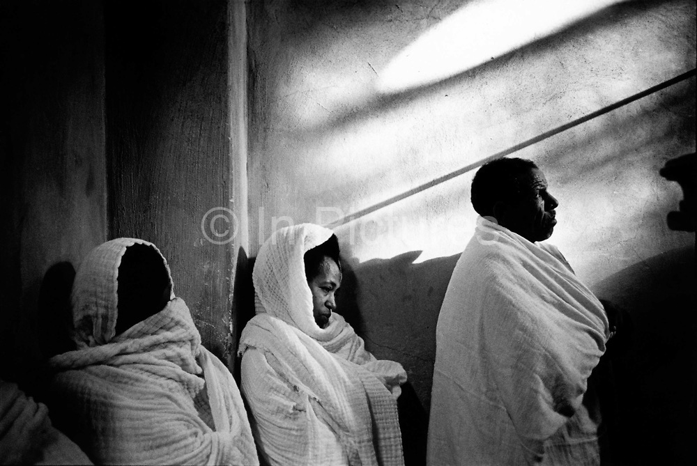 Pilgrims at prayer in the Ethiopian Orthodox Monastery built on the roof of the Holy Sepulchre Jerusalem Israel. The Ethiopians have no property in the Hly Sepulchre only access rights and have a small monastery Deir es-Sultan on the roof of a small annex.