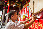 18 JUNE 2013 - YANGON, MYANMAR:  A Chinese-Burmese man pounds a prayer drum in the Kheng Hock Koeng temple in Yangon. It is the largest and busiest Chinese Buddhist/Taoist temple in Yangon.     PHOTO BY JACK KURTZ