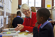 A female teacher claps and congratulates a young African school child in his literacy class in a classroom in Prestwich Primary School, Green Point, Cape Town, South Africa.  The teacher is a volunteer provided provided to the school by Shine Centre which is a charity that aims to address the high illiteracy rate in South Africa by improving literacy levels among children in schools and disadvantaged communities.