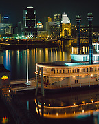 """Night view of the Cincinnati, Ohio across the Ohio River with the riverboat """"Cincinnati & New Orleans Spirit of America in the foreground, Covington, Kentucky."""