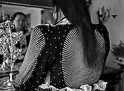 A Finnish Roma woman dressed in traditional dress in front of a mirror in a Roma home in Uppsala, Sweden