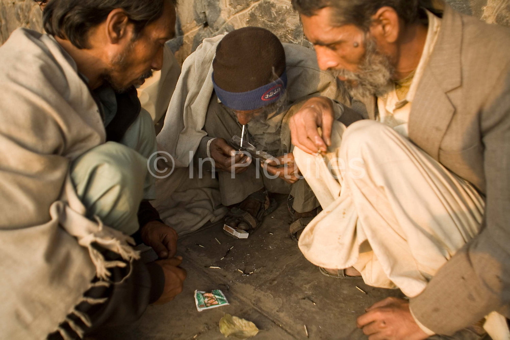 A group of homeless men smoke cheap heroin in an area full of the homeless, destitute and poor near the Jama Masjid. Delhi, India<br /> It is estimated that around than 150000 people - more than one percent of the city - is homeless and, with constant migration this is increasing on a daily basis. The incidence of mental illness amongst this group is very high. Delhi has little formal provision to deal with such a situation
