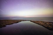 Long exposure nightshot, with view to infinity. Startrails reflecting into water   Nattbilde med lang eksponering med utsikt til evigheita. Stjernespor som reflekterer i sjøen.