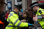 Police officers arrect protesters on Whitehall on 16th October 2019 in England, United Kingdom.  Extinction Rebellion climate activists sit down in the road despite the police imposing a section 14 of the Public Order Act 1986  in effect banning all protest by the group in London.
