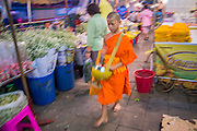 09 OCTOBER 2012 - BANGKOK, THAILAND:  A novice Buddhist monk walks through the Bangkok Flower Market. Most males in Thailand enter the Sangha (become Buddhist monks) at least once in their lives. Their time in the Sangha may be as short as a few weeks or as long as a lifetime commitment. The Bangkok Flower Market (Pak Klong Talad) is the biggest wholesale and retail fresh flower market in Bangkok. It is also one of the largest fresh fruit and produce markets in the city. The market is located in the old part of the city, south of Wat Po (Temple of the Reclining Buddha) and the Grand Palace.    PHOTO BY JACK KURTZ