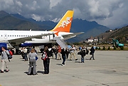 Tourists descend from a Druk Air flight on the runway at Paro airport, PBH. Paro Dzong can be seen in the background. Paro, Druk Yul, Kingdom of Bhutan. 10 November 2007