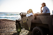 Couple parked in their landrover on the slipway at St Ouen's Bay, Jersey, CI, taking photos of the surf, beach and sea