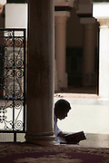 A man sits quietly, reading the Koran in a mosque in the medina of Fes, Morocco