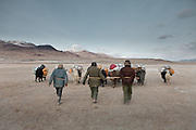 Wakhi men leading a yak caravan with their walking sticks..Trekking with yak caravan through the Little Pamir where the Afghan Kyrgyz community live all year, on the borders of China, Tajikistan and Pakistan.