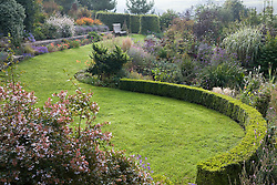 Curving lawn and late summer borders on a misty morning