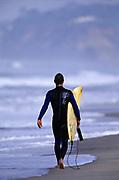 Male surfer walking on the beach in San Diego, CA.