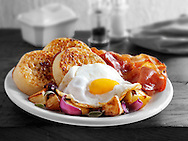 Breakfast with crumpets, fried egg, bacon and sauteed potatoes stock photos