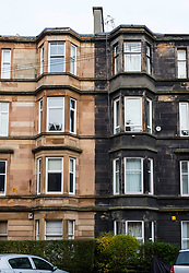 View of typical  sandstone tenement apartment buildings , one after cleaning and the other without cleaning still showing black sooty discolouration in Govanhill district of Glasgow, Scotland, United Kingdom