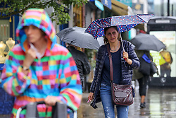 © Licensed to London News Pictures. 25/07/2021. London, UK. A woman shelters under an umbrella from a heavy downpour in north London., after the recent heatwave.  According to The Met Office, torrential thunderstorms are expected in the capital. Photo credit: Dinendra Haria/LNP
