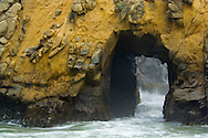 Waves washing through hole in coastal rock cliff at Pfeiffer Beach, Big Sur Coast, Monterey County, California
