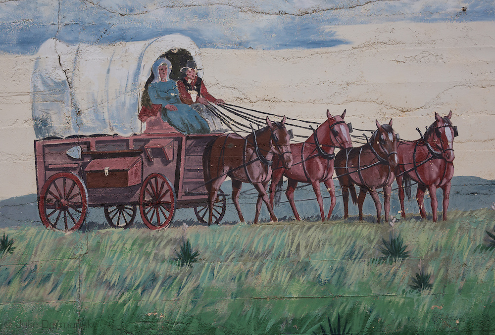 Mural depicting the wild west on a building in Syracuse Colorado.