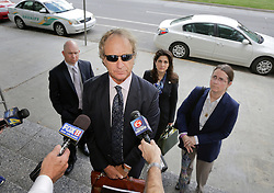 11 June  2015. New Orleans, Louisiana. <br /> Attorney Randy Smith addresses the media outside Civil District Court. In background <br /> L/R Ryan LeBlanc, Rita Benson LeBlanc and their mother Renee LeBlanc,prepare for another day at the hearing to determine the competency of grandfather/father Tom Benson. Benson is the billionaire owner of the NFL New Orleans Saints, the NBA New Orleans Pelicans, various auto dealerships, banks, property assets and a slew of business interests. Rita, her brother and mother demanded a competency hearing after Benson changed his succession plans and decided to leave the bulk of his estate to third wife Gayle, sparking a controversial fight over control of the Benson business empire.<br /> Photo©; Charlie Varley/varleypix.com
