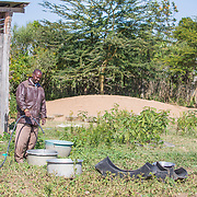 INDIVIDUAL(S) PHOTOGRAPHED: Zaberid Gitouga Daniel. LOCATION: Lamuria, Matanya, Laikipia County, Kenya. CAPTION: Daniel fills up buckets of water for his livestock to drink from at his home in Kenya's rural Laikipia County. He recently had one of SunCulture's solar-powered systems installed. The kit pulls water from a borehole into the water storage tank, and the solar panels provide the pump's electricity without need for expensive batteries. Previously, Daniel and his wife spent many hours each day fetching water for their livestock. With SunCulture's system in place, he's now able to spend more time growing cash crops such as onions, harvesting four times the yield he previously got.