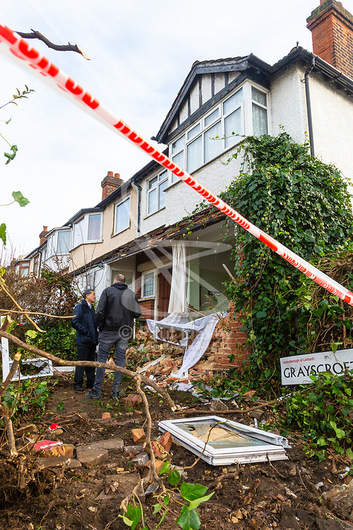 Neighbours examine the scene at the corner of Grayscroft Road and  Streatham Vale in South London where a 118 bus crashed into a house on December 26th. The house was empty at the time, the tenants who lived there having a lucky escape as they had vacated the premises on Christmas Eve. LONDON, December 27 2018.