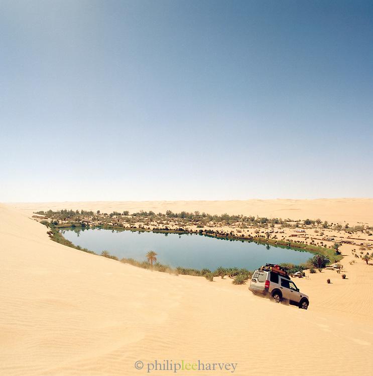 A 4x4 desends a sand dune by Gebraoun Lake, part of the Ubari lakes in the Sahara Desert, Libya