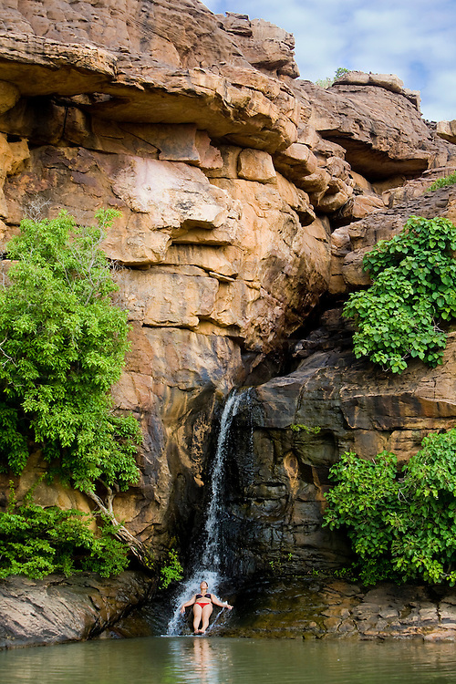 Tourist baths on a waterfall on the ascent from Kani-Kombolé to  Djiguibombo village. Waterfalls formed during the rainy season drop from the Bandiagara Escarpment cliff permitting tourists to cool off from the hiking. The Dogon Country is the most visited part of Mali with tourists visiting its tipical  villages that can be located on the cliff, on the sandy plain or in the rocky plateau