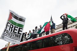 Pro-Palestinian demonstrators climb on top of a double-decker bus outside Downing Street as thousands of people attend an emergency rally in solidarity with the Palestinian people organised by Palestine Solidarity Campaign, Friends of Al Aqsa, Stop The War Coalition and Palestinian Forum in Britain on 11th May 2021 in London, United Kingdom. The rally took place in protest against Israeli air raids on Gaza, the deployment of Israeli forces against worshippers at the Al-Aqsa mosque during Ramadan and attempts to forcibly displace Palestinian families from the Sheikh Jarrah neighbourhood of East Jerusalem.
