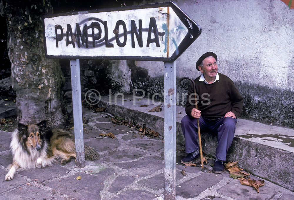 A road sign for Pamplona and man villager sitting with his dog, Navarra, Spain.