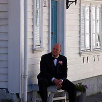 Europe, Norway, Stavanger. Norwegian Groom in Stqavanger watches his bride being photographed.