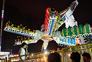 Visitors enjoy an amusement ride at the carnival grounds of the Qingdao (Tsingtao) Beer Festival in Qingdao, China on 27 August, 2011. Named after the locally brewed Tsingtao Beer, one of China's most famous exports, the festival has grown from a local binge drinking feast to an internationally known festival.