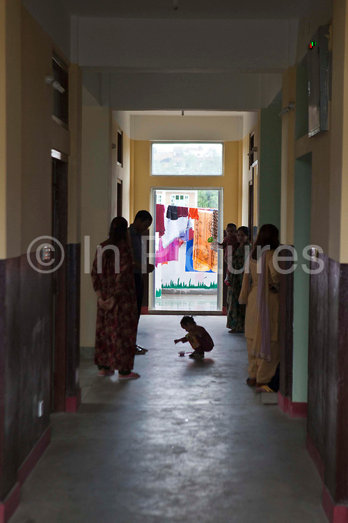A Nepalese child plays in the middle of the corridor while mother and staff from the Friends of Needy Children Nutritional Rehabilitation Home talk.  Kathmandu, Nepal.  Washing is hanging to dry outside the centre. The clinic has recently been built.  It treats malnourished children and provides education to mothers about nutrition and childcare.