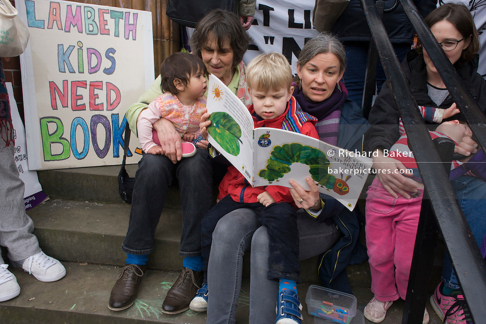 Mothers read to their children while protesting on the steps of Carnegie Library in Herne Hill, south London while occupiers remain inside the premises on day 5 of its occupation, 4th April 2016. The angry local community in the south London borough have occupied their important resource for learning and social hub for the weekend. After a long campaign by locals, Lambeth have gone ahead and closed the library's doors for the last time because they say, cuts to their budget mean millions must be saved. A gym will replace the working library and while some of the 20,000 books on shelves will remain, no librarians will be present to administer it.