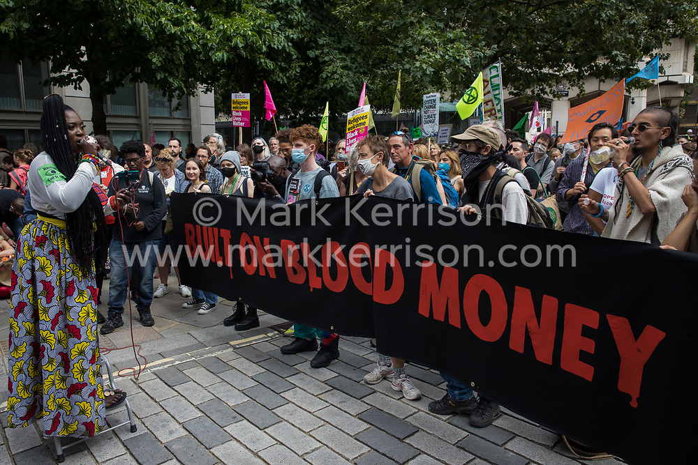 London, UK. 27th August, 2021. Marvina Newton addresses environmental activists from Extinction Rebellion after fake blood was spread outside the offices of law firm Debevoise & Plimpton LLP during a Blood Money March through the City of London on the fifth day of Impossible Rebellion protests. Extinction Rebellion were intending to highlight financial institutions funding fossil fuel projects, especially in the Global South, as well as law firms and institutions which facilitate them, whilst calling on the UK government to cease all new fossil fuel investment with immediate effect.