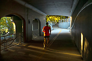 A runner passes through the Broadway Bridge tunnel into Julia Davis Park in late afternoon