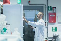 Young male scientist reading notes in a pharmacy laboratory, Freiburg im Breisgau, Baden-Wuerttemberg, Germany