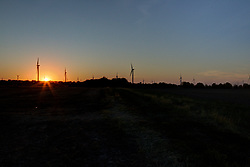 19 October 2017:   The autumn sun sets behind an already harvested soybean field and the wind turbines in the White Oak Wind Farm between Hudson, Normal and Carlock Illinois