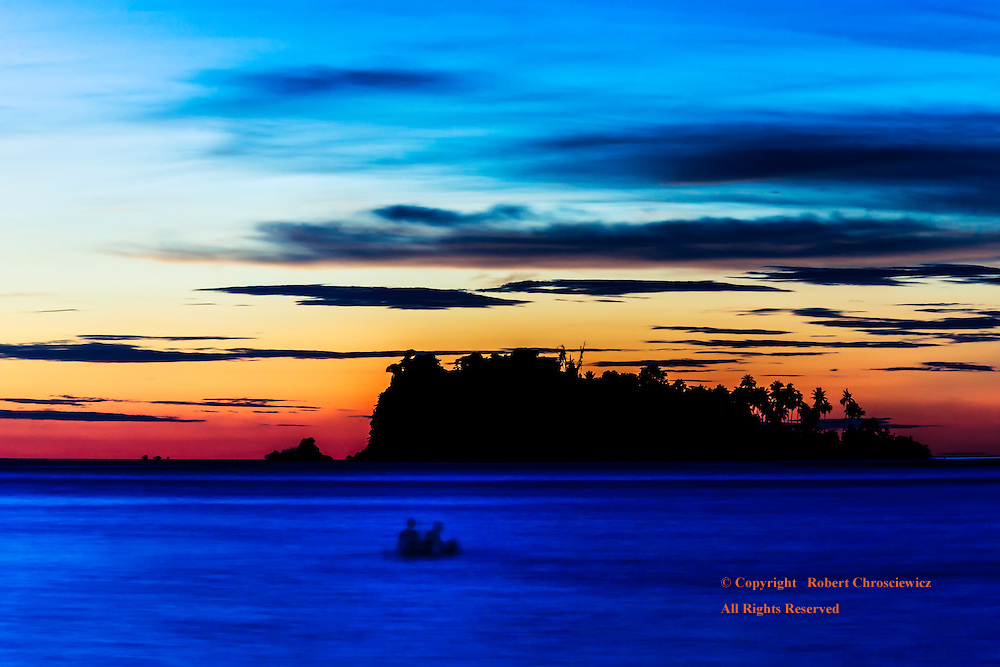Goodnight Ko Chang: A pair of silhouetted swimmers frolics in the waves under the waning light, Lonely Beach - Ko Chang Thailand.