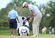 June 12 2013: Matt Harmon's coach kneels on the green to video tape his putting motion on an iPad during the wednesday practice round at the 2013 U.S. Open hosted by Merion Golf Club in Ardmore, PA.