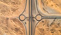 Aerial view of geometrical roundabout and roads in the desert of Umm Al Quawain, U.A.E.