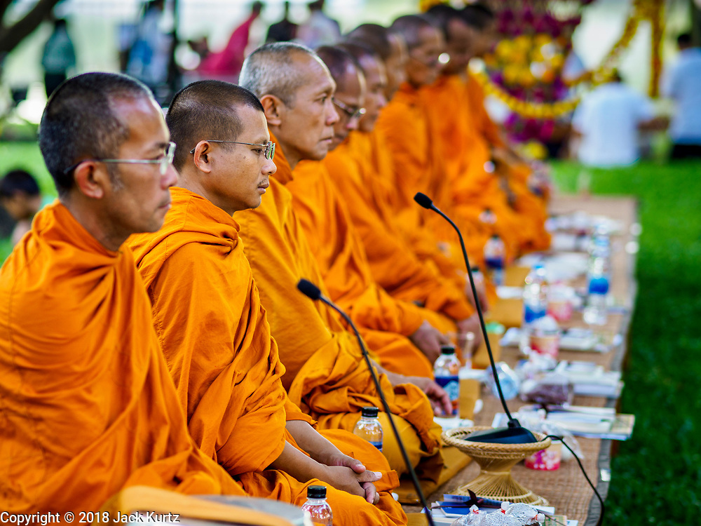 """17 MARCH 2018 - BANGKOK, THAILAND:  Buddhist monks lead a prayer during a """"sticky rice merit making"""" in Lumpini Park in Bangkok. Sticky rice merit making is a merit making in the Isan / Lao style, when people present small amounts of cooked sticky rice (also known as glutinous rice) to Buddhist monks. Isan is the northeast region of Thailand.    PHOTO BY JACK KURTZ"""