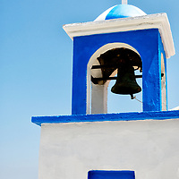 Samos. Greece. Bell tower with cross from the blue white washed Greek Orthodox Church at the Northern seaside town of Avlakia. In the background are the dazzling blue waters of the Aegean Sea.