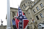 7/1/2020 Today is the last day for the Mississippi State flag bearing the Confederate emblem to be flown over the state Capitol. Alfred Thomas, right and Alfred McClinton both employees of the Mississippi State Capitol are seen raising and lowering commemorative State flags. They raised and lowered over 100 flags today, that have been purchased by people from all around the world, and they have each flown over the Capitol, just hours after Governor Tate Reeves signed a historic Bill HB1796 decommissioning the state flag and opening the door to a new flag without the Confederate emblem that has flown for 126 years.Photo copyright © Suzi Altman @suzialtman #mississippi #flag #history #change #equality #progress #confederateflag