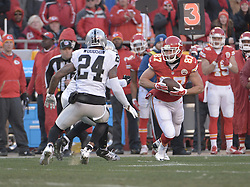 Jan 3, 2016; Kansas City, MO, USA; Kansas City Chiefs tight end Travis Kelce (87) catches a pass as Oakland Raiders free safety Charles Woodson (24) defends during the first half at Arrowhead Stadium. Mandatory Credit: Denny Medley-USA TODAY Sports
