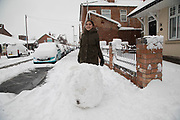 Girl having fun in Kings Heath in heavy snow fall building a snow man on Sunday 10th December 2017 in Birmingham, United Kingdom. Deep snow arrived in much of the UK, closing roads and making driving treacherous, while many people simply enjoyed the weather.