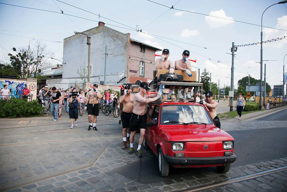 """Francis Thorburn's work, """"Fiat 126 MK DRP1800 18202764"""", part of the New Art From London show. The Fiat car had been made unable to drive and was pushed by a bunch of half naked men with the help of a wooden tread mill from the out skirts of Wroclaw and to the gallery. OUT of STH Vol.3 at Awangarda Gallery. Two shows at once, Les Fleurs du Mal - New Art from London curated by Cedar Lewisohn and Free Ride Art Space / bicycle exhibition curated by Blandine Roselle. The shows run 30 April - 17 June."""