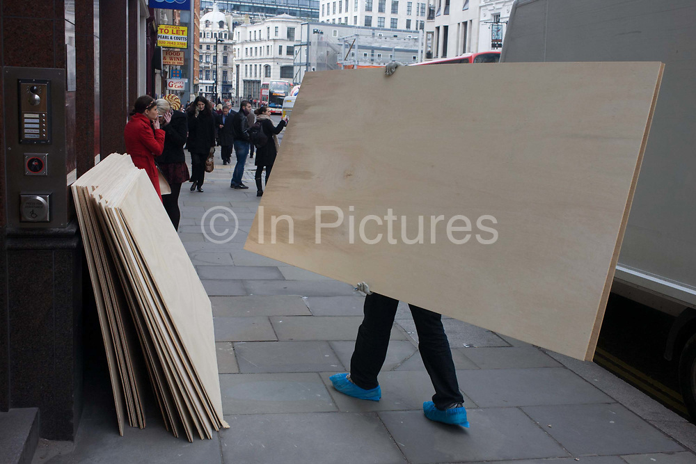 Delivery man carries the last sheet of plyboard for local construction project. Carrying the boards from a waiting white van to a pile of similars in this City of London street, the unseen person wears protective plastic shoe covers that helps preserve the office floors nearby. In the background are Londoners on this City of London street pavement in the heart of the capital's financial district. Ongoing works are happening all over the City as improvements continue and improve the working environment for office workers.