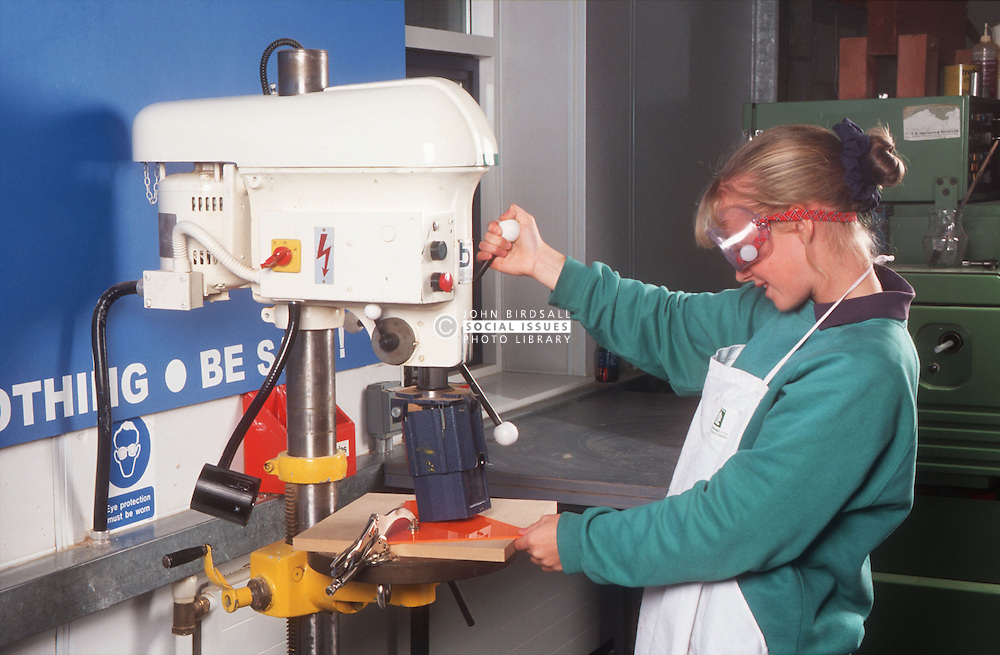 Design and technology student wearing safety goggles operating machine to drill through piece of plastic,